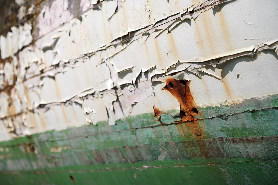 Flaking paint on a wooden sailboat.